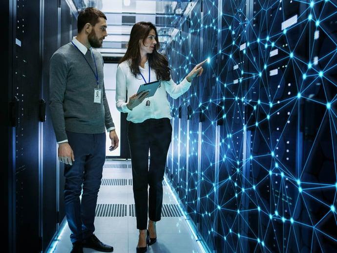 Ingenieros de TI hombres y mujeres discuten detalles técnicos en un centro de datos de trabajo