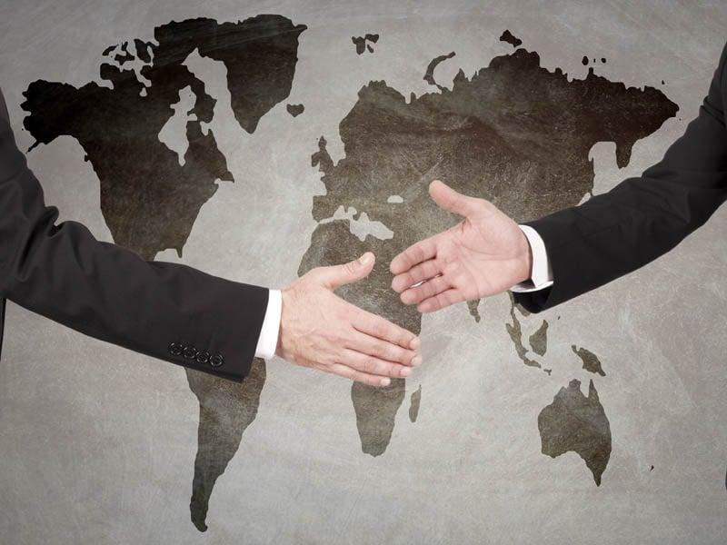 Licenciados en relaciones internacionales dándose la mano frente a un mapa mundial.