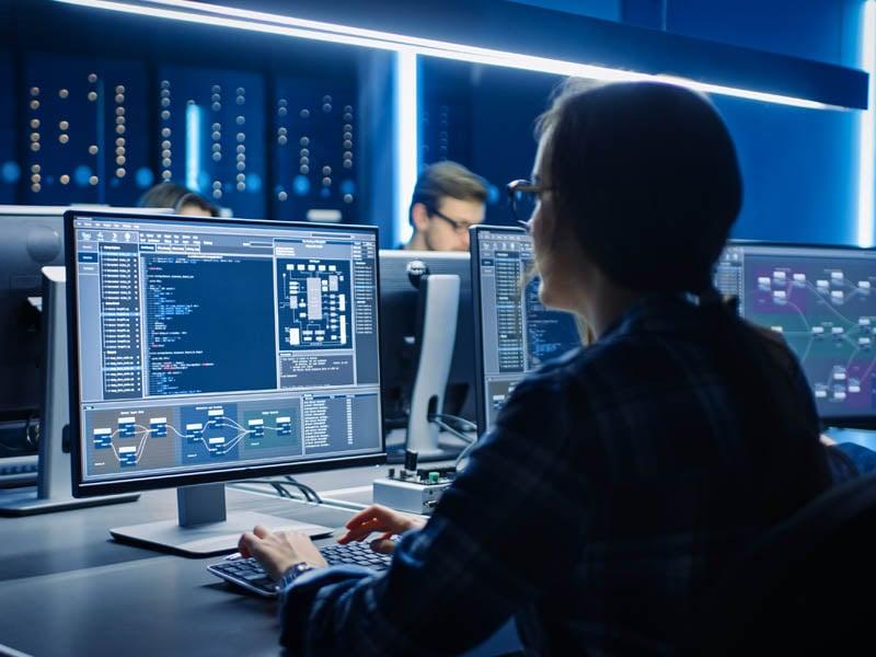 Mujer programadora IT trabajando en computadora de escritorio